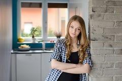 Schöne blauäugige blonde Frau steht auf der Wand in der Küche still Lizenzfreie Stockfotografie
