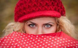 Schöne blaue Augen über buntem Regenschirm. Attraktives blondes Mädchen mit der roten Kappe, die über dem roten Regenschirm im Fre Stockbilder