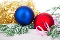 Schöne blaue und rote Weihnachtsbälle auf eisigem Tannenbaum Eine Abbildung einer blauen Blumenverzierung mit Schatten Stockfoto