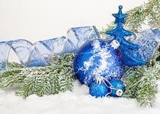 Schöne blaue Weihnachtsbälle auf eisigem Tannenbaum Eine Abbildung einer blauen Blumenverzierung mit Schatten Lizenzfreies Stockfoto