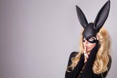 Schöne blond-haarige junge Frau im Karnevalsmasken-Ballsaalkaninchen mit sinnlichem sexy der langen Ohren in einem schwarzen Klei Stockfotografie