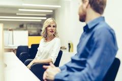 Schöne blonde Arbeitskraft, die mit Kollegen im Büro spricht Lizenzfreies Stockfoto
