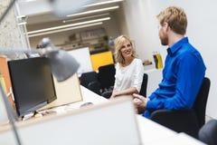 Schöne blonde Arbeitskraft, die mit Kollegen im Büro spricht Lizenzfreies Stockbild