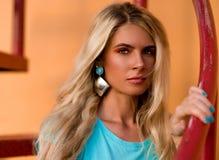 Schöne blonde Aufstellung an der Kamera Porträt auf dem Hintergrund der Leuchtorangewand Modernes Hippie-Mädchen nahaufnahme Stockfoto