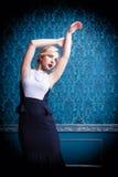 Schöne blonde Aufstellung im blauen Innenraum der Weinlese Stockbild