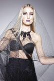 Schöne blonde Aufstellung mit einem schwarzen Schleier Lizenzfreies Stockfoto