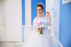 Schöne blonde Aufstellung nahe einer weißen Spalte in einem Hochzeitskleid mit einem Blumenstrauß von zarten rosa Pfingstrosen Lizenzfreies Stockfoto