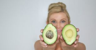 Schöne blonde Avocadofrau vor Kamera, Nahaufnahme Stockfoto