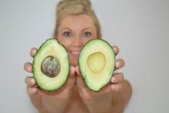 Schöne blonde Avocadofrau vor Kamera, Nahaufnahme stockfotografie