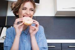 Schöne blonde Bisse des süßen Donuts Ungesundes Lebensmittel, Bonbons Stockfoto