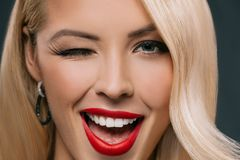 schöne blonde blinzelnde Frau, lokalisiert Stockfotografie