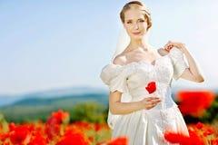 Schöne blonde Braut auf dem Gebiet mit Mohnblumen Lizenzfreies Stockbild