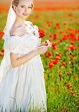 Schöne blonde Braut auf dem Gebiet mit Mohnblumen Lizenzfreie Stockfotografie