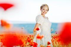 Schöne blonde Braut auf dem Gebiet mit Mohnblumen Lizenzfreie Stockfotos