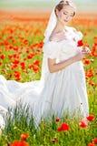 Schöne blonde Braut auf dem Gebiet mit Mohnblumen Stockfotos