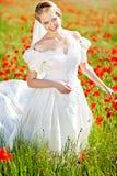 Schöne blonde Braut auf dem Gebiet mit Mohnblumen Lizenzfreies Stockfoto