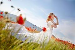 Schöne blonde Braut auf dem Gebiet mit Mohnblumen Stockfoto