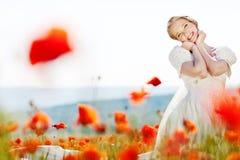 Schöne blonde Braut auf dem Gebiet mit Mohnblumen Stockbild