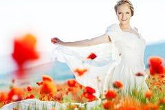 Schöne blonde Braut auf dem Gebiet mit Mohnblumen Lizenzfreie Stockbilder