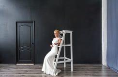 Schöne blonde Braut der jungen Frau auf der hölzernen Treppe im Innenraum im Studio Stockfoto