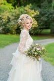 Schöne blonde Braut in der Park whith Hochzeit Stockfotografie