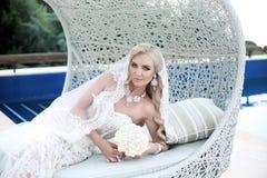 Schöne blonde Braut des Hochzeitsporträts, die auf Strandsofa in f liegt Stockbild