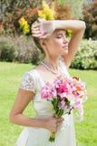 Schöne blonde Braut, die Arm zur Stirn hält Lizenzfreies Stockfoto