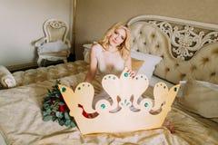 Schöne blonde Braut, die auf Bett mit großer handgemachter Krone in den Händen sitzt Lizenzfreies Stockfoto