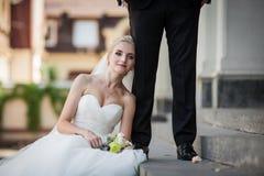 Schöne blonde Braut, die auf der Treppe, lehnend am handso sitzt Lizenzfreie Stockfotografie