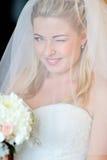 Schöne blonde Braut, die Auge blinzelt Lizenzfreie Stockfotos