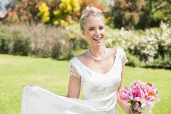 Schöne blonde Braut, die Blumenstrauß halten und ihr Kleid, das an der Kamera lächelt Lizenzfreie Stockfotos