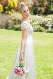 Schöne blonde Braut, die den Blumenstrauß betrachtet Kamera hält Stockbilder