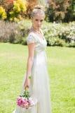 Schöne blonde Braut, die den Blumenstrauß weg schaut hält Stockfotografie