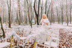 Schöne blonde Braut, die in den Herbstwaldweinlese-Hochzeitsstühlen auf Vordergrund aufwirft Stockbild