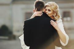 Schöne blonde Braut, die hübschen Bräutigam im schwarzen Mantel in t küsst Lizenzfreies Stockbild
