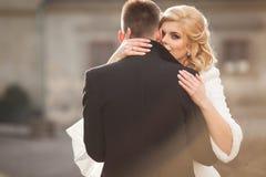 Schöne blonde Braut, die hübschen Bräutigam im schwarzen Mantel in t küsst Lizenzfreie Stockfotografie