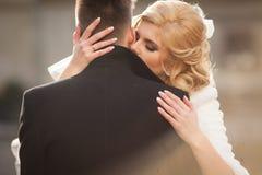 Schöne blonde Braut, die hübschen Bräutigam im schwarzen Mantel in t küsst Lizenzfreies Stockfoto