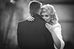 Schöne blonde Braut, die hübschen Bräutigam im schwarzen Mantel in t umarmt Lizenzfreie Stockbilder