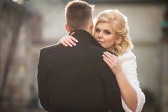 Schöne blonde Braut, die hübschen Bräutigam im schwarzen Mantel in t umarmt Stockfoto