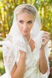 Schöne blonde Braut, die ihren Schleier hält Lizenzfreies Stockfoto