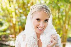 Schöne blonde Braut, die ihren Schleier lächelt an der Kamera hält Lizenzfreies Stockbild
