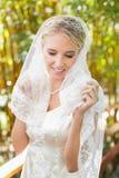 Schöne blonde Braut, die ihren Schleier und Lächeln berührt Stockfotos
