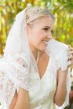 Schöne blonde Braut, die ihren Schleier und Lächeln hält Stockbild