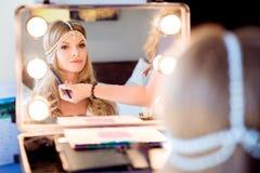 Schöne blonde Braut, die Make-up in ihrem Hochzeitstag nahe mirro tut Stockfoto