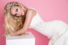 Schöne blonde Braut in einem Hochzeitskleid auf einem Schwingen verziert Lizenzfreie Stockfotografie