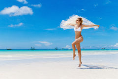 Schöne blonde Braut in einem weißen Bikini und in einem Schleier, die Spaß O haben Lizenzfreie Stockbilder