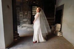 Schöne blonde Braut im eleganten weißen Hochzeitskleid, das herein aufwirft Lizenzfreie Stockfotos