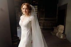 Schöne blonde Braut im eleganten weißen Hochzeitskleid, das herein aufwirft Stockbild