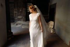 Schöne blonde Braut im eleganten weißen Hochzeitskleid, das herein aufwirft Stockfotos
