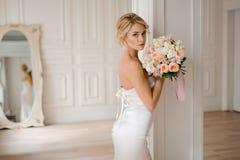Schöne blonde Braut im eleganten weißen Kleid, das einen Hochzeitsblumenstrauß hält Lizenzfreies Stockbild